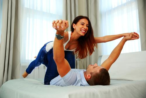 happy-couple-playing-bed